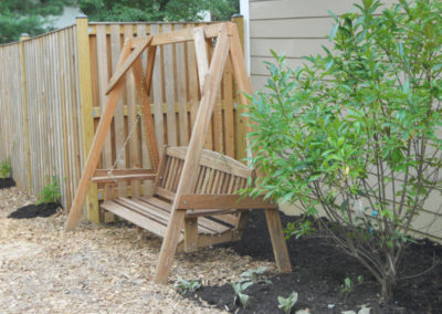 Swinging bench with a fringe tree and lambs ears in the texture garden