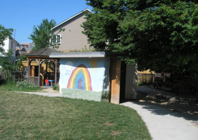 A shunnel (shed + tunnel) built with stacked straw bales covered with lime plaster and a rainbow mural